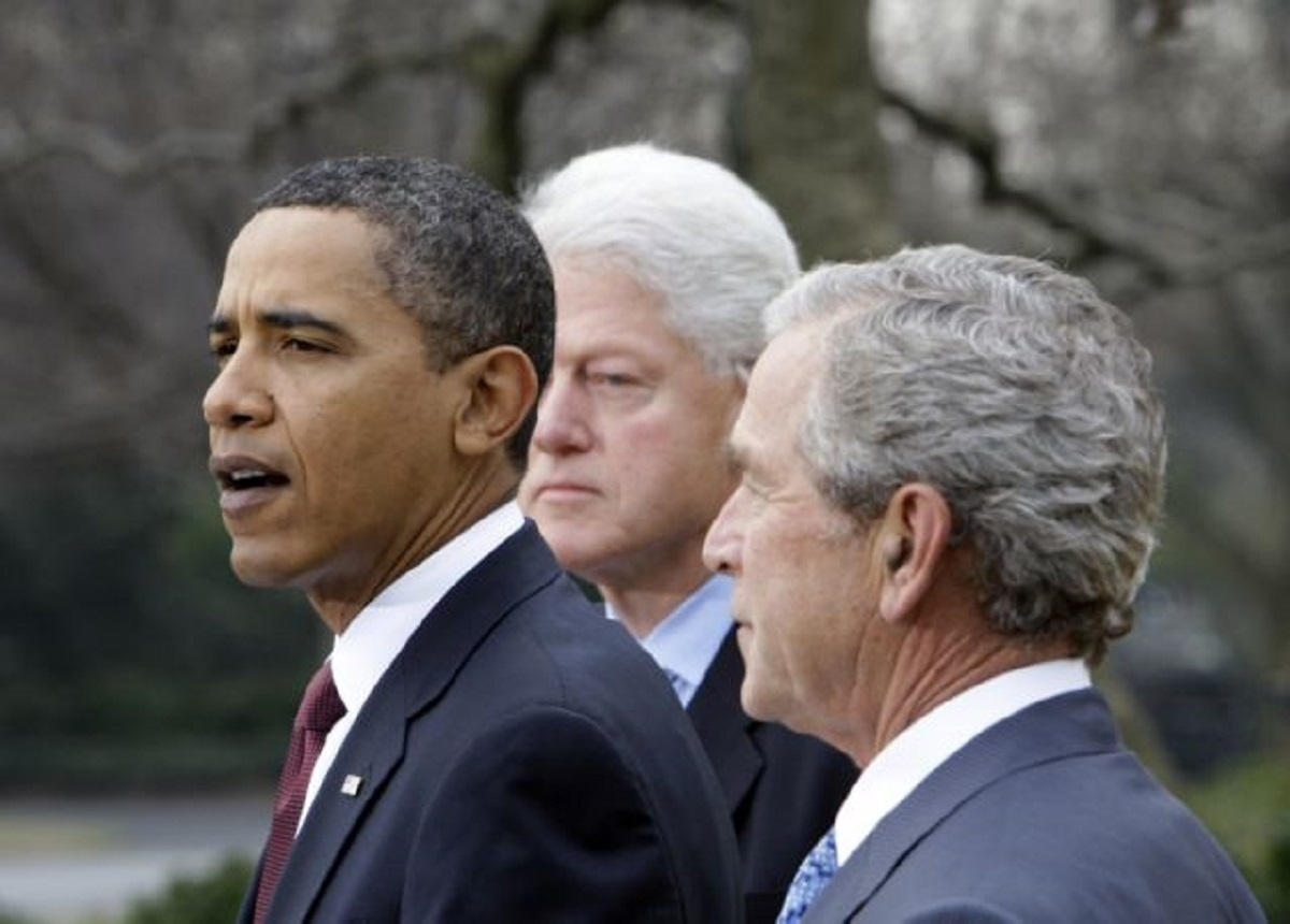 President Barack Obama speaks as former Presidents Bill Clinton and George W. Bush listen in the Rose Garden at the White House in Washington Saturday, Jan. 16, 2010. Obama asked former presidents Clinton and Bush to help with U.S. relief efforts in Haiti after the earthquake.   (AP Photo/Alex Brandon)